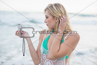 Attractive blonde woman in white beach dress taking a picture of herself