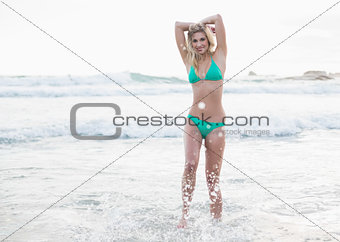 Happy blonde woman in green bikini posing looking at camera