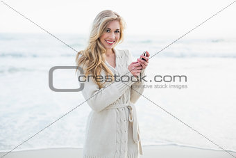 Smiling blonde woman in wool cardigan using a mobile phone