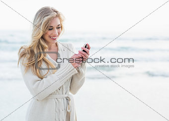 Pleased blonde woman in wool cardigan using a mobile phone