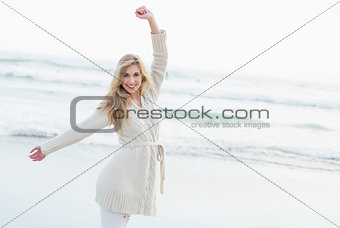 Joyful blonde woman in wool cardigan stretching her arms