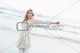 Amused blonde woman in wool cardigan stretching her arms