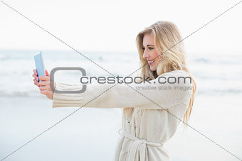 Amused blonde woman in wool cardigan taking a picture of herself with a tablet pc