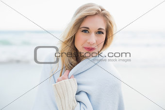Content blonde woman covering herself in a blanket