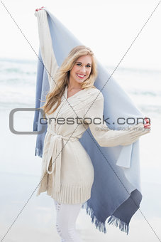 Delighted blonde woman shaking her blanket