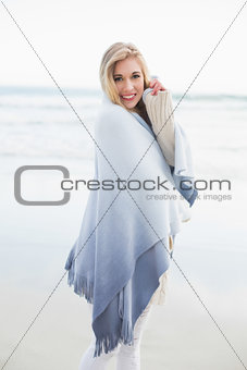 Charming blonde woman covering herself in a blanket