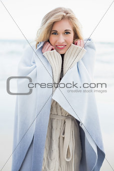 Smiling blonde woman covering herself in a blanket