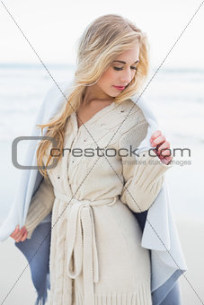 Calm blonde woman covering herself in a blanket