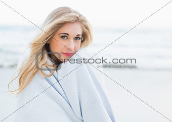 Calm blonde woman warming herself in a blanket