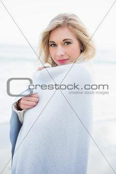 Pleased blonde woman warming herself in a blanket
