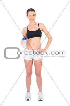 Peaceful woman in sportswear holding flask