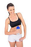 Smiling toned woman in sportswear holding flask