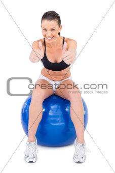 Positive woman in sportswear sitting on exercise ball giving thumbs up to camera