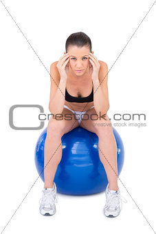 Worried fit woman sitting on exercise ball