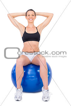 Happy fit woman working out with exercise ball