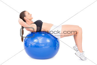 Smiling fit woman working out with exercise ball