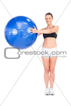 Happy fit woman working out using exercise ball