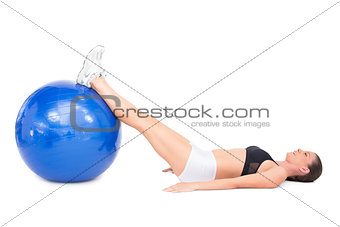 Side view of fit woman lying working out with exercise ball