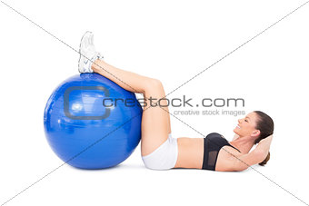Fit woman developing her abs using exercise ball