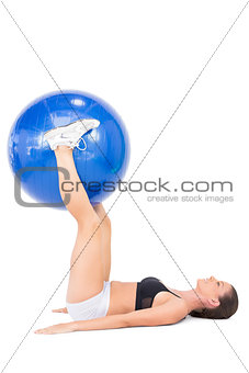 Smiling athletic woman working out with exercise ball