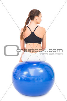 Rear view of fit woman sitting on exercise ball