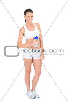 Happy woman in sportswear holding flask smiling at camera