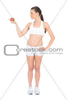 Fit woman in sportswear holding red apple