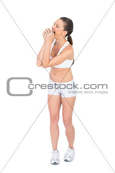 Fit woman in sportswear munching apple