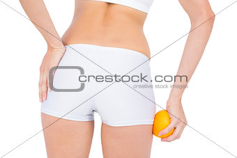 Rear view of fit woman massaging her buttocks