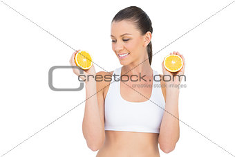 Fit woman holding slices of orange