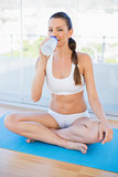 Fit young woman sitting in lotus position drinking