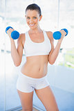 Smiling woman lifting dumbbells