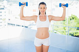 Concentrated sporty woman lifting dumbbells