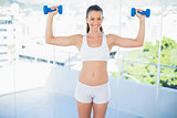 Happy sporty woman lifting dumbbells