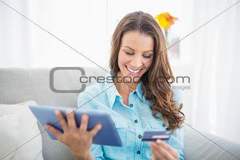 Attractive brunette holding tablet and credit card
