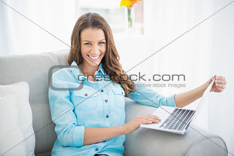 Smiling woman holding laptop sitting on couch
