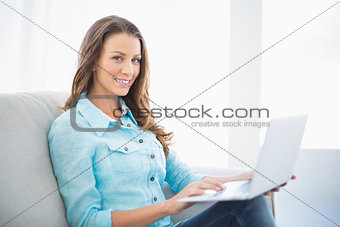 Smiling brunette sitting on sofa using laptop