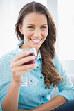 Cheerful gorgeous brunette holding glass of red wine