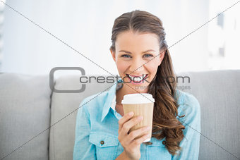 Portrait of attractive smiling woman holding cup of coffee