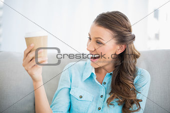 Smiling woman looking at her coffee