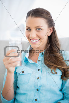Portrait of attractive woman holding glass of water