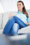 Serious woman sitting on sofa