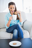 Happy woman dunking biscuit into hot chocolate