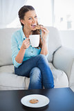 Happy woman holding cup of coffee eating cookie