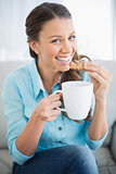 Smiling woman eating cookie holding cup of coffee