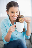 Smiling woman dunking cookie in coffee