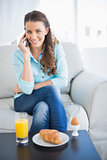 Smiling woman on the phone sitting on sofa