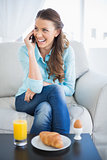 Smiling woman talking on the phone sitting on sofa