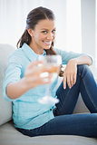 Smiling woman showing glass of white wine at camera