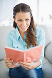 Smiling woman sitting on sofa reading book